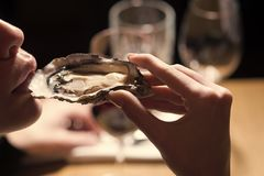 Woman eating shellfish. Seafood and Mediterranean cuisine with mussels in shell. Young woman eating oyster in luxury Royalty Free Stock Photo