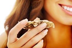 Woman eating shellfish. Young beautiful woman eating raw shellfish Royalty Free Stock Photography