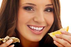 Woman eating shellfish. Young beautiful woman eating raw shellfish with lemon Royalty Free Stock Photos