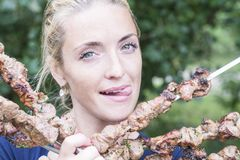 Woman sticking out her tongue with pleasure. Woman is eating a shish kebab on a skewer and sticking out her tongue with pleasure royalty free stock photos