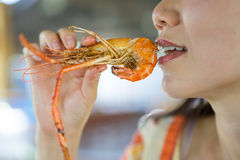 Woman eating a shrimp Royalty Free Stock Image