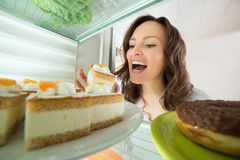 Woman Eating Slice Of Cake From Fridge. Hungry Young Woman Eating Slice Of Cake From Fridge At Home stock image