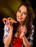 Woman eating slice of Italian pizza. Student consume fast food. Stock Photography