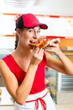 Woman eating a slice of pizza Stock Images