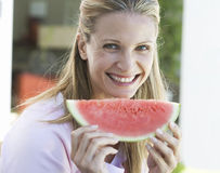 A woman eating a slice of watermelon Royalty Free Stock Photo