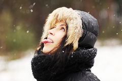 Woman eating snowflakes. Happy beautiful woman playing outdoor, trying to catch snowflakes with her tongue Royalty Free Stock Photos
