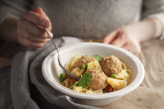 Woman eating spaghetti with meatballs from a bowl Royalty Free Stock Photos
