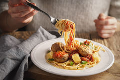 Woman eating spaghetti with meatballs and cheese Royalty Free Stock Images
