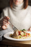 Woman eating spaghetti with meatballs Stock Photos