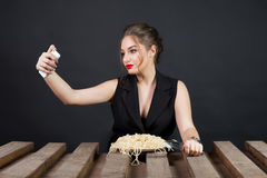 Woman eating spaghetti and taking selfie royalty free stock photos