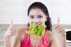 Woman eating spinach while showing OK sign Stock Image