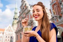 Woman eating sprats in Riga city Stock Photo