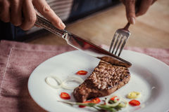 Woman eating steak. Close-up partial view of woman eating steak with fork and knife royalty free stock photos