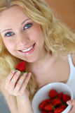 Woman eating strawberries Royalty Free Stock Images