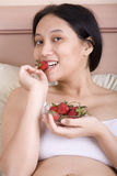 Woman eating strawberry. Pregnant woman enjoying her strawberry Royalty Free Stock Photography