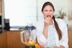 Woman eating a strawberry Royalty Free Stock Image