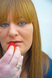Woman  eating a strawberry. Royalty Free Stock Photography