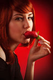 Woman eating strawberry Stock Images