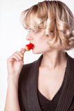 Woman   eating a strawberry Stock Images