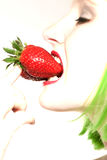 Woman eating a strawberry with a green wig Royalty Free Stock Photo
