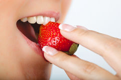 Woman eating strawberry. Happy young woman eating red juicy strawberry Royalty Free Stock Photography