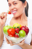 Woman eating strawberry and holding fruits stock photos