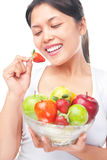 Woman eating strawberry & holding fruits Royalty Free Stock Images