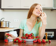 Woman eating strawberry in home kitchen Royalty Free Stock Image