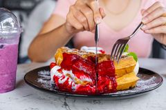 Woman eating strawberry waffles with knives and forks stock photos