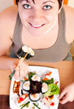 Woman eating sushi Stock Images