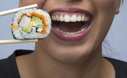 Woman eating sushi. With chopsticks Royalty Free Stock Photo