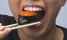 Woman eating sushi Stock Photos
