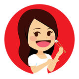 Woman Eating Sushi. Cute young woman eating salmon sushi with chopsticks Royalty Free Stock Image