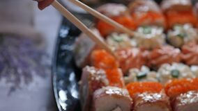 Woman eating sushi in restaurant Japanese cuisine, uses chopsticks. close-up rolls slow motion. Woman eating sushi in restaurant Japanese cuisine, uses stock video