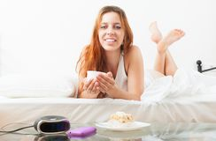Woman eating sweet cake and cafe at bed Stock Photos