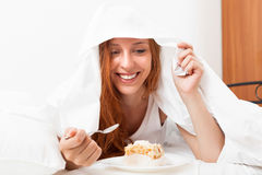 Woman eating sweet cake under sheet in bed Stock Photos