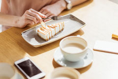 Woman eating sweet dessert while sitting in cafe, coffee break Royalty Free Stock Image