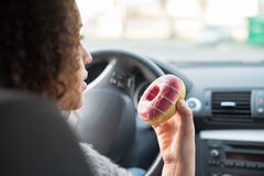 Woman eating a sweet driving a car. Woman eating a sweet driving her car Royalty Free Stock Photography