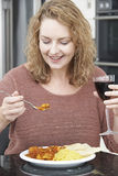 Woman Eating Takeaway Curry And Drinking Wine Royalty Free Stock Photography