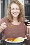 Woman Eating Takeaway Curry And Drinking Wine Royalty Free Stock Image