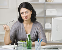 Woman Eating a Tasteless Lunch. A young woman is eating lunch in her office.  She is looking at the camera.  Horizontally framed shot Stock Photos