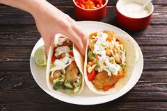 Woman eating tasty fish taco. At wooden table royalty free stock photos