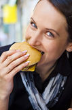 Woman eating tasty hamburger Stock Photography