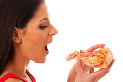 Woman eating tasty piece of pizza. Unhealthy fast food meal. Isolated over white Royalty Free Stock Image