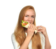 Woman eating tasty unhealthy burger twisted sandwich in hands Stock Images