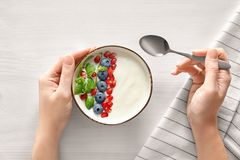 Woman eating tasty yogurt with blueberry. And pomegranate seeds at wooden table Royalty Free Stock Photo