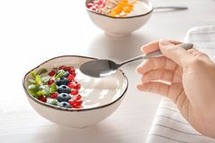 Woman eating tasty yogurt with blueberry. And pomegranate seeds at wooden table Royalty Free Stock Image