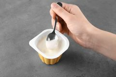 Woman eating tasty yogurt. At grey table Stock Image