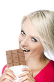 Woman eating a tempting bar of chocolate Royalty Free Stock Images