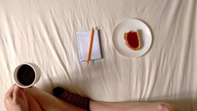 Woman is eating toast with jam and drinking coffee on the bed, top view hd video. Girl is eating toast and drinking coffee on the bed, top view hd video stock footage